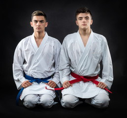 two guys karate on a dark background