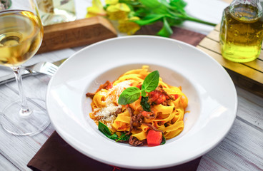pasta tagliatelle with pieces of beef, tomatoes and Basil on white plate. serving at the restaurant