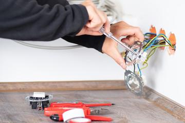 Elektriker bei der Arbeit an einer Steckdose
