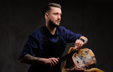 Chef cook cutting exclusive jerky meat on a table in a hunting house on dark background.