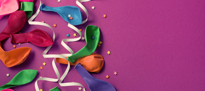 Banner Festive background of purple material colorful balloons streamers confetti Top view flat lay copy space