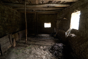 Old rustic clay cowshed interior with window and manure for fertilizer inside