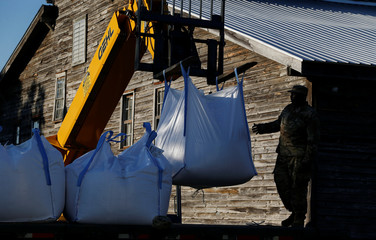 A member of the National Guard works to unload sand bags in anticipated floods in downtown, caused by Hurricane Florence, now downgraded to a tropical depression, in Conway