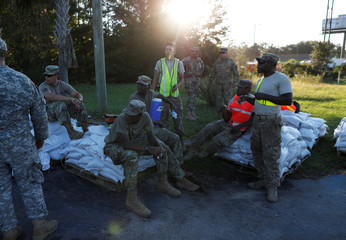 Members of the National Guard take a break while working on a long sand bag flood barrier being built by the South Carolina Department of Transportation on U.S. 501 to lesson damage to roads anticipated from floods caused by Hurricane Florence