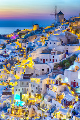 Travel Concepts. Skyline of Oia Town with Traditional White Architecture and Iconic Windmills in Village of Santorini in Greece.World Famous Resort.