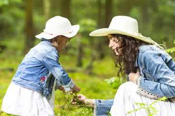 Family Ideas and Concepts. Tranquil and Positive Caucasian Couple of Mother and Little Daughter Having Time Together in Green Summer Forest.