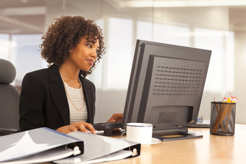Young businesswoman using computer at desk indoors office building