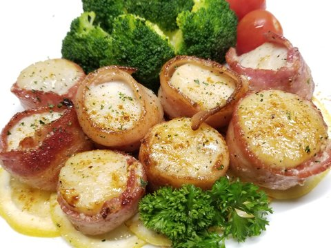 Bacon wrapped scallops on a white background