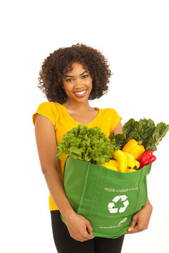 Beautiful young African woman carrying healthy groceries isolated on white