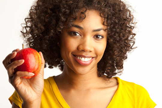 Close up of young African woman smilling and holding apple