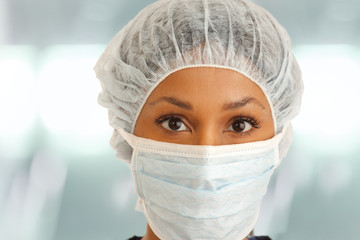 Close up of female surgeon wearing mask and hair net inside hospital