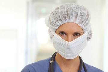 Close up portrait of serious young woman doctor in scrubs with mask and cap