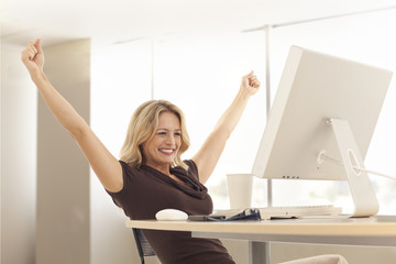 Young businesswoman stretching at desk inside office building