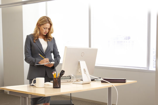 Young businesswoman writing at desk indoors office building