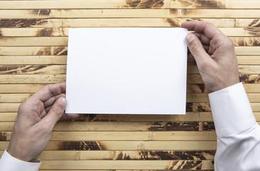 Mens hand holding white letterhead