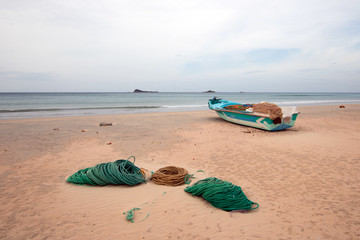 Small coastal fishing boat next to ropes and nets on Nilaveli Beach in Trincomalee state in Sri Lanka Asia