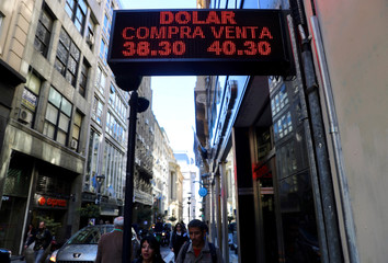 People walk beneath a currency exchange board in Buenos Aires' financial district