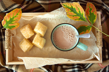 Cocoa with milk in a ceramic mug and puff pastry in a wooden box, surrounded by a checkered scarf.