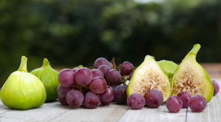 Figs and grapes on a white wooden table top
