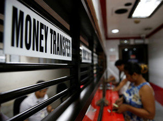 Customers receive money from families working abroad at a money remittance center in Makati