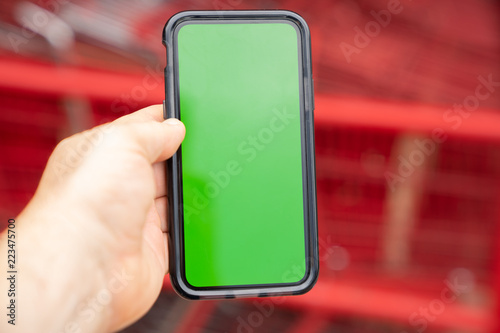 Man holding green screen smart phone with blurred shopping carts in