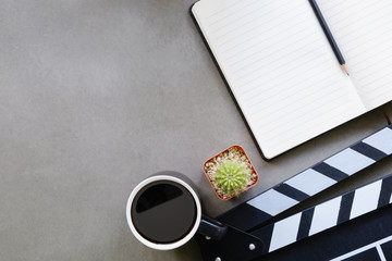 Movie clapper with notepad paper ,cup of coffee, cactus on director table top view and copy space.