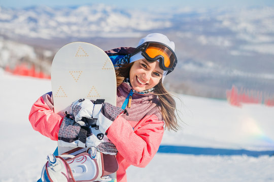 smiling young woman with snowboarding on the mountain in winter