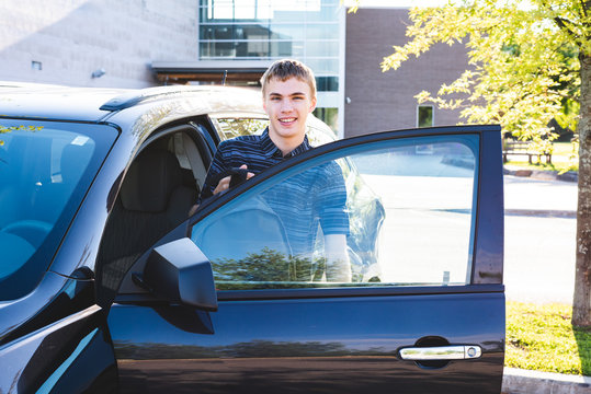 Teenager stepping out of his car on the first day of school.