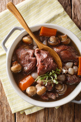 Traditional French food: Coq au vin cock with wine and vegetables, thyme close-up in a pot. Vertical top view from above