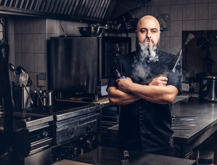 Bearded chef in black uniform smoking e-cigarette while standing in the kitchen.