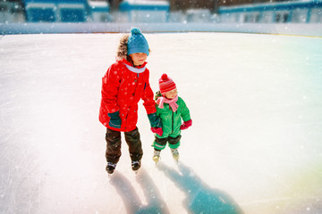 brother teaching little sister to skate in winter