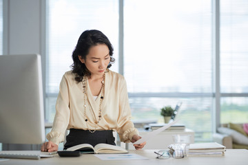Young Chinese business lady reading documents on her table