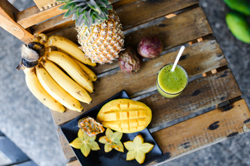 Pine apple with bananas, carambola and mango standing on wooden chair, kiwi fresh juice. Concept of healthy food and exotic diet.