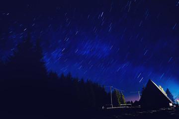 Star trails with countryside suburb silhouettes at night.