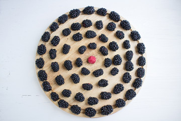 Set of many blackberries and raspberry on round wooden tray
