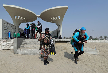 Dana Al Qatari and her fellow diver Zynab Al Magaslah walk towards sea to dive at Half Moon Beach open water dive side in Dhahran