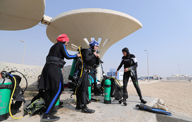 Saudi female diver helps her diving partner to get ready for a dive at Half Moon Beach open-water dive site in Dhahran