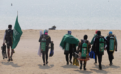 Saudi female divers walk to the sea with their trainer holding Saudi national flag at Half Moon Beach open-water dive site in Dhahran