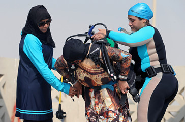 Women help their fellow diver to wear her diving equipment as they get ready to dive at Half Moon Beach open-water dive site in Dhahran