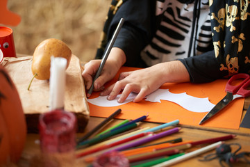 Hands of little boy drawing bat on colored paper for Halloween party
