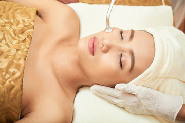 Pretty young Vietnamese woman getting microdermabraision procedure at cosmetologist