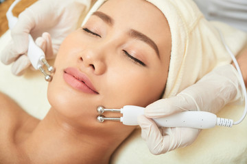 Attractive young woman enjoying microcurrent procedure in spa salon