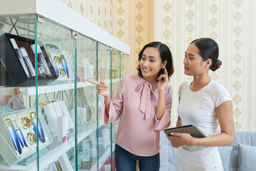 Pretty young woman asking beautician about cosmetics on shelves in beauty salon