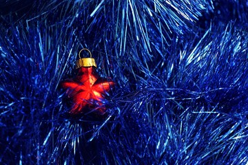 New Year's red ball on a background of blue tinsel.
