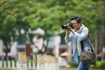 Vietnamese young photographer enjoying taking photos in city park