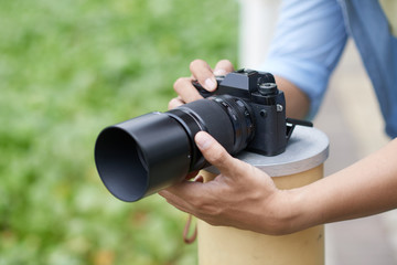 Photographer putting digital camera on fence column to take best photos