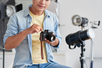 Cropped image of professional photographer checking his camera before shooting in studio