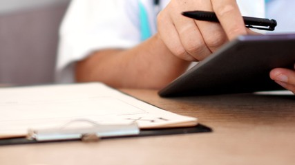 Medical doctor working with digital tablet computer and writting rx prescription for patient