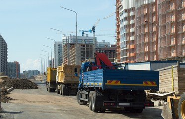 Trucks, construction machinery and high-rise cranes on the construction site.