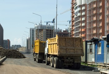 Yellow trucks stand on the roads near the construction site